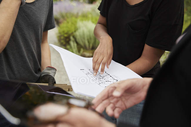 Midsection of female garden architect explaining blueprint to colleagues — Stock Photo