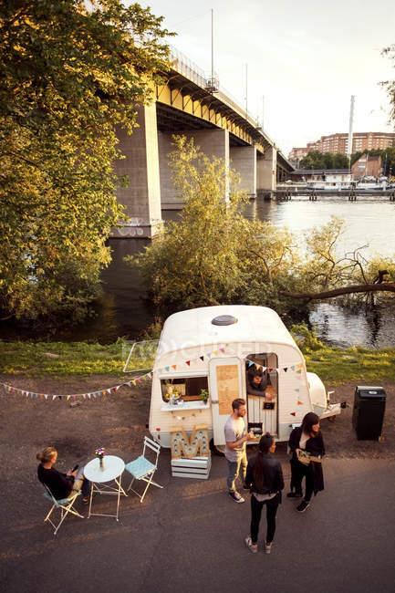Blick auf Kunden und Foodtruck-Besitzer auf der Straße mit Brücke im Hintergrund — Stockfoto
