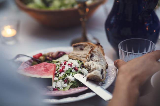 Imagem cortada do homem que tem comida à mesa durante a festa no jardim — Fotografia de Stock