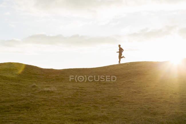 Fernsicht des Mannes, der an sonnigen Tagen auf einem Grashügel gegen den Himmel joggt — Stockfoto