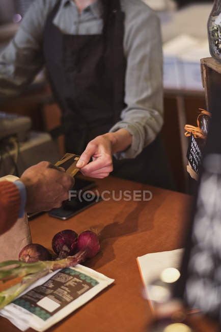 Cropped image of customer doing credit card payment to owner at store — Stock Photo