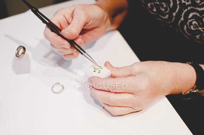 Cropped image of senior female craftsperson assembling jewelry in workshop — Stock Photo