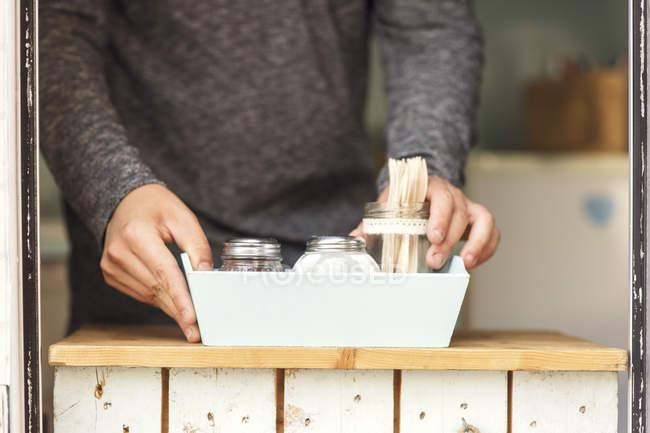 Mitte des männlichen Besitzers platziert Salz- und Pfefferstreuer mit Gabeln im Container am Foodtruck-Fenster — Stockfoto
