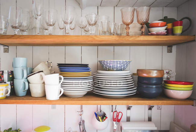 Crockery and drinking glasses on shelves in kitchen at home — Stock Photo