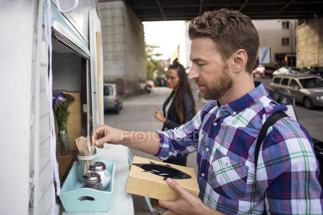 Männliche Kundin entfernt Gabel aus Container vor Food-Truck mit Frau im Hintergrund — Stockfoto