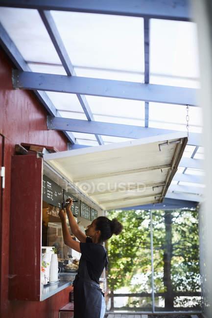 Вид сбоку официантки, пишуй в меню в кафе — стоковое фото