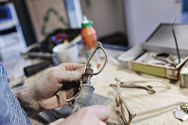 Zugeschnittenes Bild des Besitzers machen Brillen mit Arbeitsgerät in Werkstatt — Stockfoto