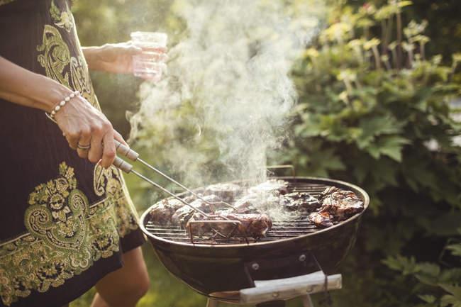 Животик женщины жарки мяса на барбекю на заднем дворе — стоковое фото