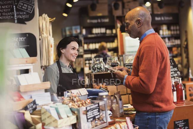 Sorridente proprietario parlando con il cliente tenendo pacchetto in piedi al negozio — Foto stock