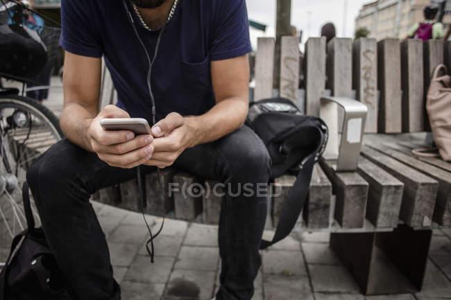 Животик человека с помощью мобильного телефона сидя на деревянной скамейке в городе — стоковое фото