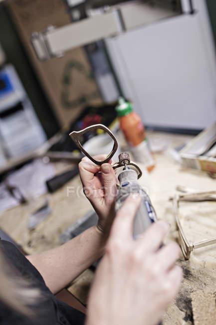 Zugeschnittenes Bild der weibliche Besitzer machen Brillen mit Arbeitsgerät in Werkstatt — Stockfoto