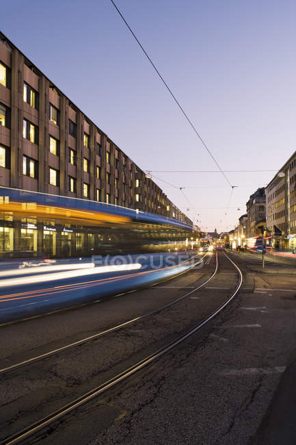Bewegliche Straßenbahn auf Stadtstraße in der Abenddämmerung — Stockfoto