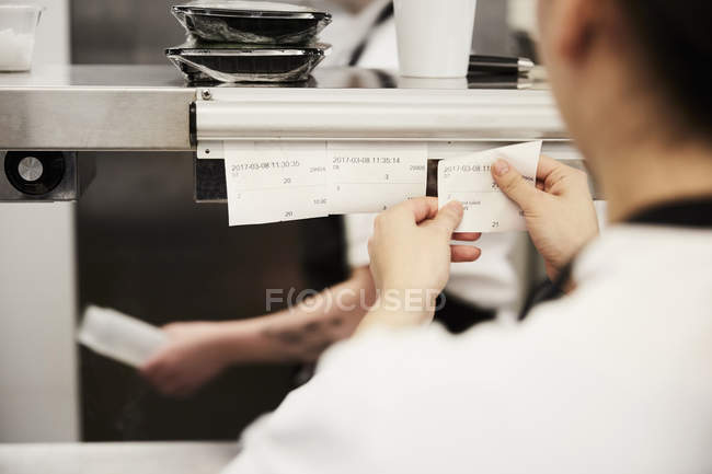 Cropped image of female chef reading order tickets in commercial kitchen — Foto stock