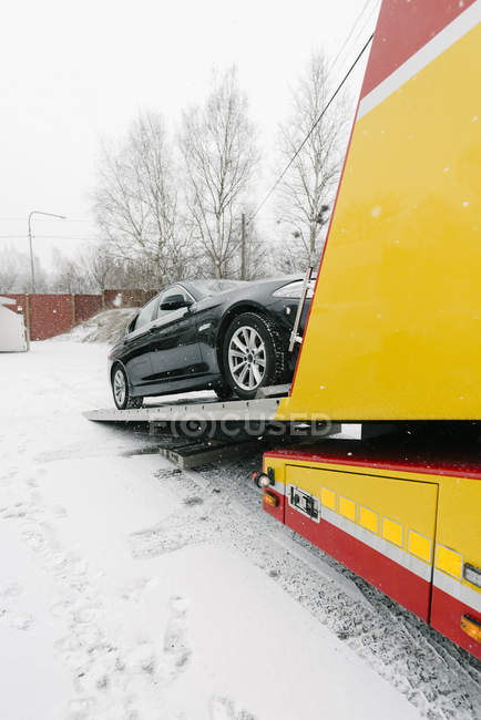 Black car on tow truck during winter — Stock Photo