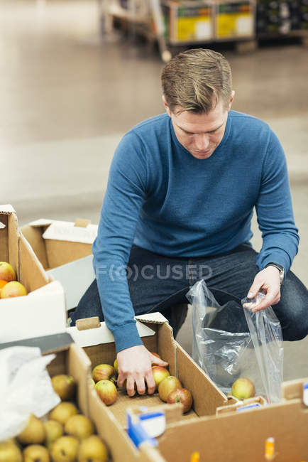 High angle view of owner putting apples in plastic bag from cardboard box at supermarket — Stock Photo