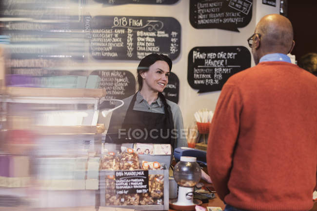 Proprietario parlando con il cliente mentre in piedi al banco cassa in negozio — Foto stock