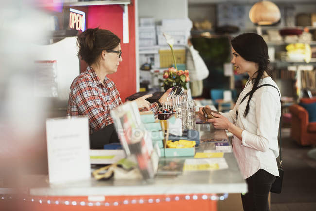 Owner showing drinking glasses to customer while standing at checkout counter in store — Stock Photo