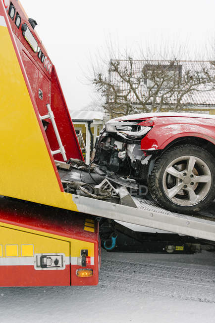 Damaged car on tow truck during winter — Stock Photo