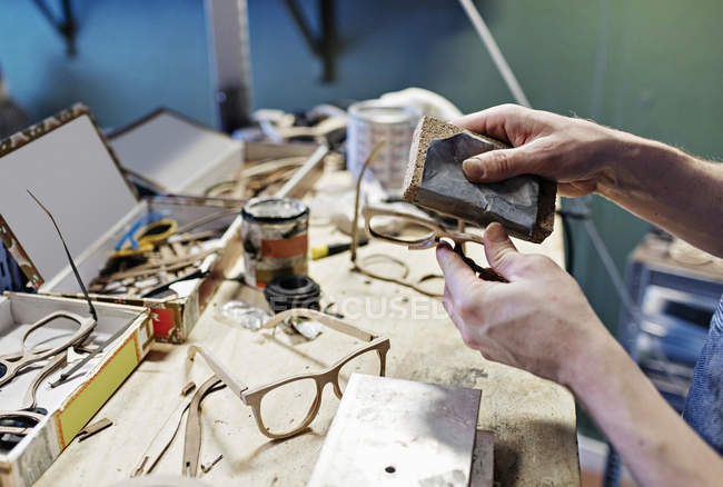 Cropped image of male owner rubbing eyeglasses with work tool at workshop — Stock Photo