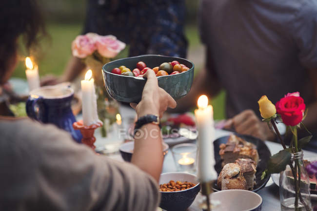 Cropped image of woman serving food to friends at garden party — Stock Photo