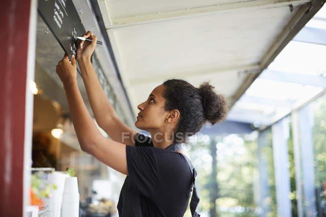 Вид сбоку молодой официантки, пишуй в меню в кафе — стоковое фото