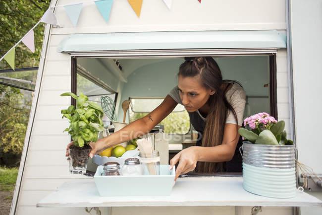 Eigentümerin arrangiert Topfpflanze am Fenster eines Imbisswagens — Stockfoto