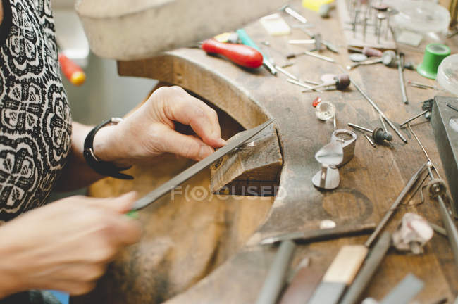 Cropped image of senior craftsperson making jewelry in workshop — Stock Photo