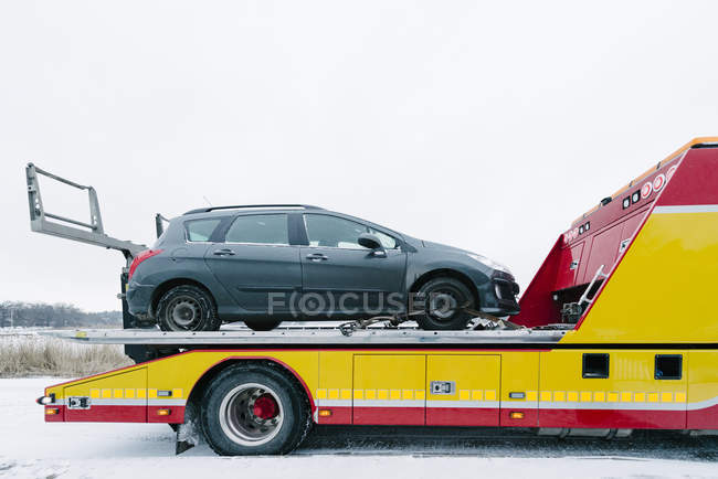 Gray car on tow truck against overcast gray sky — Stock Photo