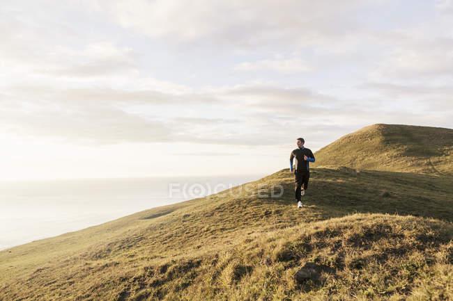 Mann joggt bei sonnigem Wetter auf Hügel am Meer — Stockfoto