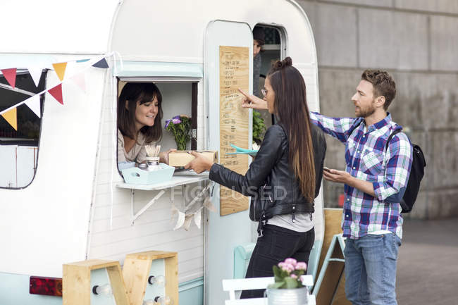 Man and woman buying food from saleswoman at food truck — Stock Photo
