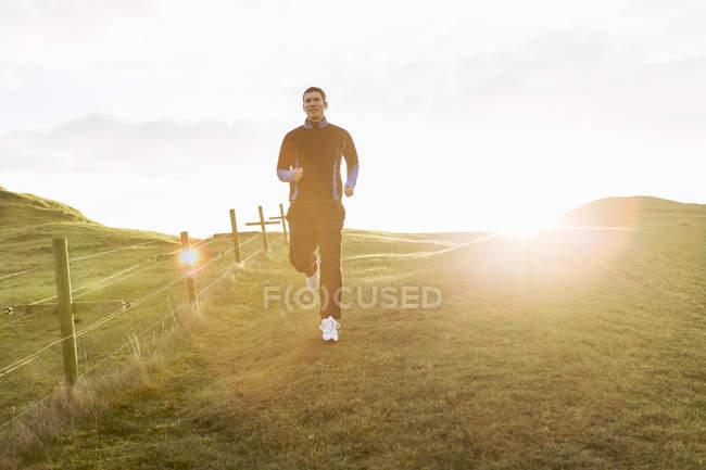 Mittlerer erwachsener Mann joggt bei sonnigem Wetter auf Wiese — Stockfoto