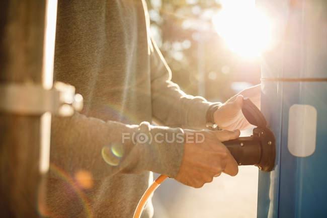 Midsection de l'homme branchant à la station électrique le jour ensoleillé — Photo de stock