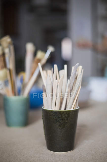 Wooden tools in container on table at workshop — Stock Photo