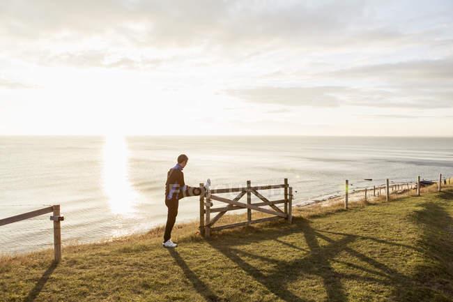 Mann streckt bei sonnigem Wetter Bein am Zaun am Strand aus — Stockfoto