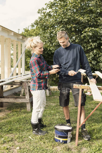 Woman showing phone to mature man while making shed at farm — Stock Photo