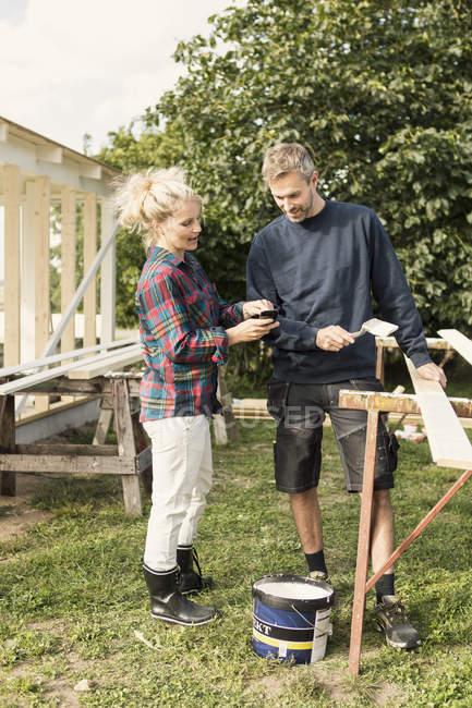 Donna che mostra il telefono all'uomo maturo mentre fa capannone in fattoria — Foto stock