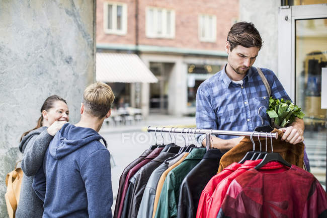 Young man selecting jackets with friends passing by clothing store — Stock Photo