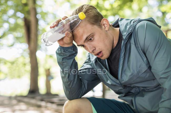 Hombre cansado jadeando mientras sostiene la botella de agua después del entrenamiento en el parque - foto de stock