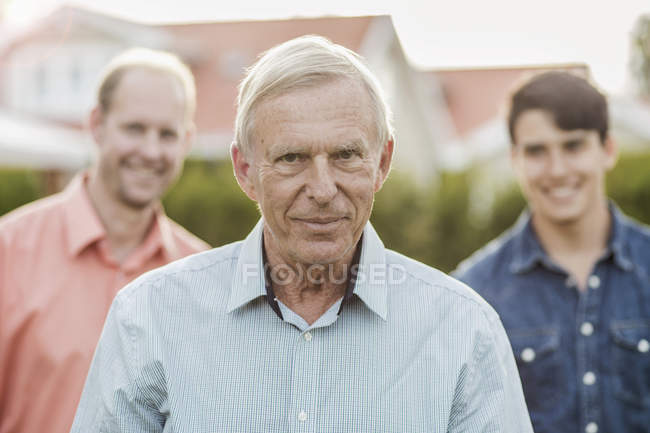 Portrait of confident senior man with son and grandson standing in yard — Stock Photo