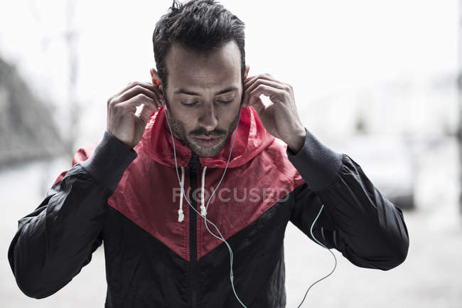 Sporty man in jacket adjusting earphones — Stock Photo