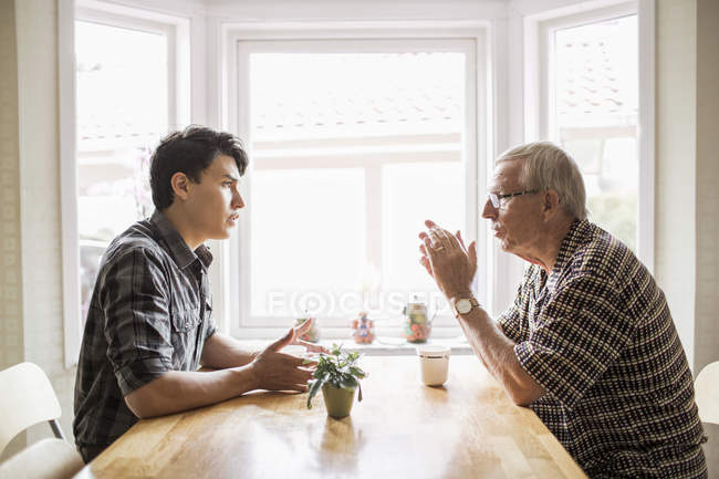 Side view of grandfather and grandson communicating while having coffee — Stock Photo