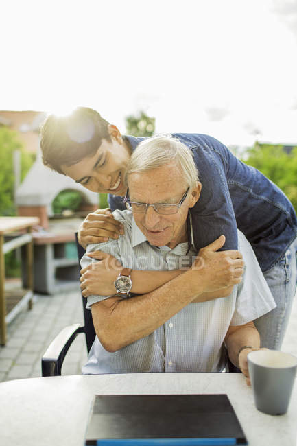 Happy young man embracing grandfather at yard — Stock Photo