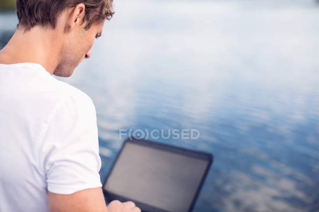 Rear view of mature man using laptop by lake — Stock Photo