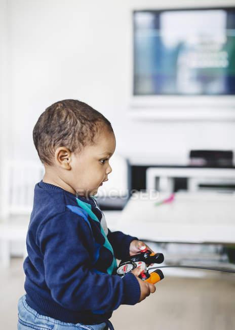 Vue latérale du garçon jouant avec faire fonctionner la télécommande de modèle réduit d'avion à la maison — Photo de stock