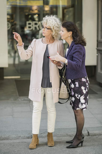Voller Länge Frauen in Führungspositionen suchen Richtung auf digital-Tablette bei Stadtstraße — Stockfoto