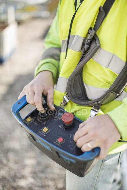 Midsection of construction worker operating control tool at site — Stock Photo