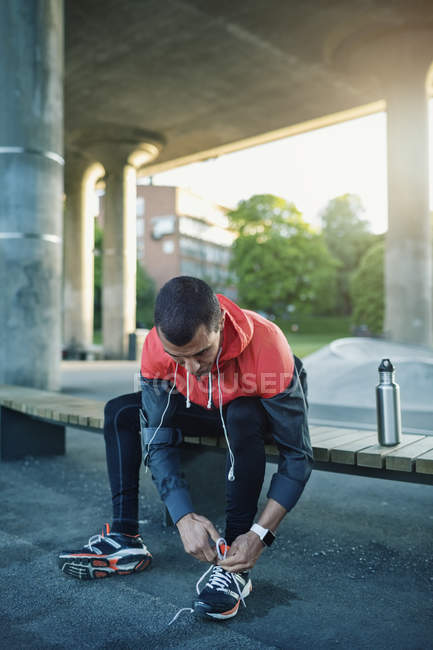 Man tying shoelace while sitting on bench under bridge — Stock Photo