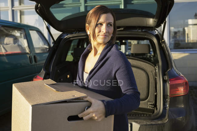 Businesswoman carrying cardboard box in front of car trunk — Stock Photo