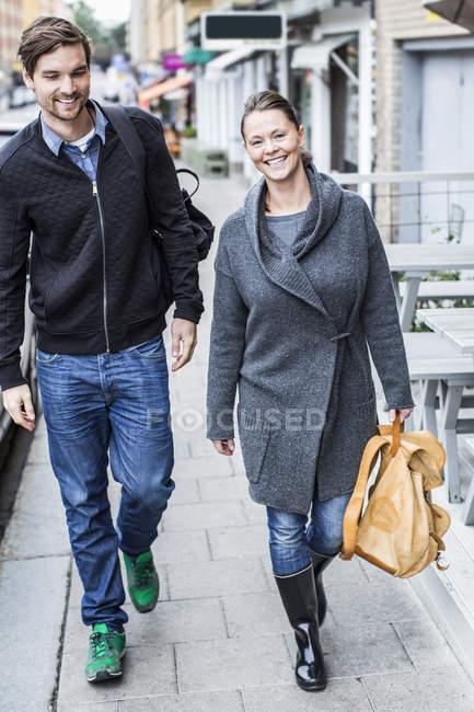 Comprimento total de amigos andando na calçada — Fotografia de Stock