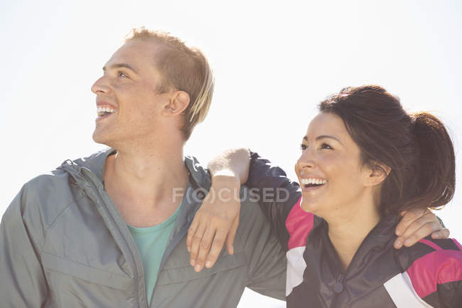 Happy fit couple looking away against clear sky — Stock Photo